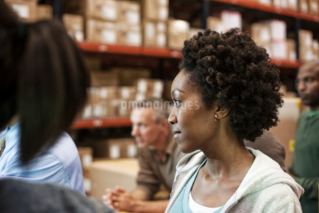 African American female warehouse worker with team of multi-ethnic workers in a large warehouse distの写真素材 [FYI02263435]