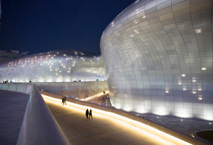 People walking along elevated walkway past illuminated contemporary curved building with translucentの写真素材 [FYI02263449]