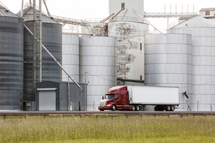 A commercial truck driving past grain elevators in the farm country of eastern Washington, USA.の写真素材 [FYI02263462]