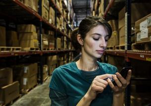 A Caucasian female warehouse worker checking her phone for texts while standing in a distribution waの写真素材 [FYI02263463]