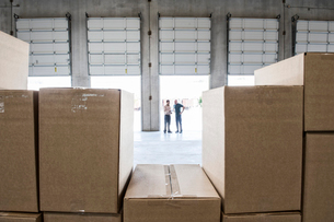 Team of workers check out inventory in front of loading dock doors in a new warehouse.の写真素材 [FYI02263465]