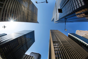 Low angle view from urban street towards clear sky, glass and steel facades of tall skyscrapers, andの写真素材 [FYI02263466]