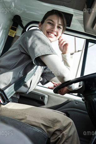 Portrait of a uniformed Caucasian female truck driver at the wheel of her truck at a distribution waの写真素材 [FYI02263474]