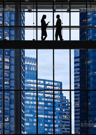Business people meeting on an elevated walkway between office buildings.の写真素材 [FYI02263489]