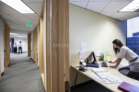 An Asian businesswoman working alone in her office next to a long hallway.の写真素材 [FYI02263497]