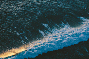 Seascape abstract at dusk, surf breaking on the shore, overhead view and sunlight on the water.の写真素材 [FYI02263511]