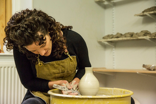 Woman with brown curly hair wearing apron shaping clay vase on pottery wheel.の写真素材 [FYI02263516]