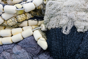 Fishing nets and floats, commercial fishing equipment in a heap on a quayside.の写真素材 [FYI02263517]