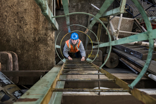 Factory worker climbing up a ladder in a sheet metal factory.の写真素材 [FYI02263518]