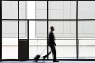 A businessman blurred in silhouette while walking past a large window in a convention centre lobby.の写真素材 [FYI02263520]