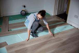 Woman laying new floorboards in the living room of  a house under renovation.の写真素材 [FYI02263535]