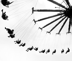 Low angle view of group of people on traditional chair swing ride.の写真素材 [FYI02263541]