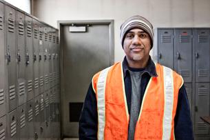 Black man factory worker standing next to lockers in a factory break room.の写真素材 [FYI02263542]