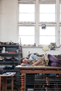 Black woman factory worker taking a nap on top of a work station in a woodworking factory.の写真素材 [FYI02263543]