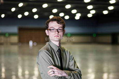 A young hip businessman standing in a dimly lit and dark exhibition area in a convention centre.の写真素材 [FYI02263547]