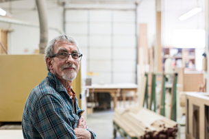 Portrait of a senior Caucasian carpenter in a large woodworking shop.の写真素材 [FYI02263554]