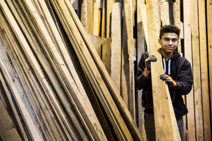 Young man wearing work gloves standing next to a stack of wooden planks in a warehouse, carrying lonの写真素材 [FYI02263558]