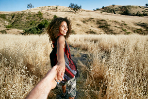 Young woman with curly brown hair hiking in urban park, holding man's hand.の写真素材 [FYI02263560]