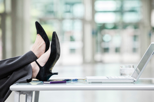 A closeup of feet and high heel shoes resting on a desk in front of a laptop computer.の写真素材 [FYI02263562]