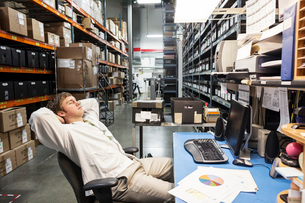 A male technician relaxing at his desk in the parts department in a technical research and developmeの写真素材 [FYI02263563]