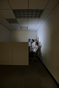 A mixed race group of three business people lit up by a desktop computer screen in a small corner cuの写真素材 [FYI02263564]