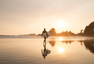 Reflection of man wearing wet suit and carrying surfboard walking along sandy beach at sunset.の写真素材 [FYI02263565]