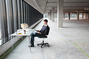 A Caucasian male business owner at his temporary desk in a new raw business space.の写真素材 [FYI02263566]