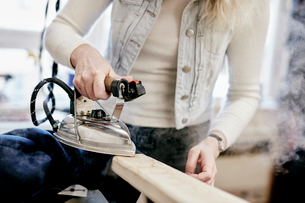 A woman using a steam iron on a new jacket, pressing the newly made garment.の写真素材 [FYI02263567]