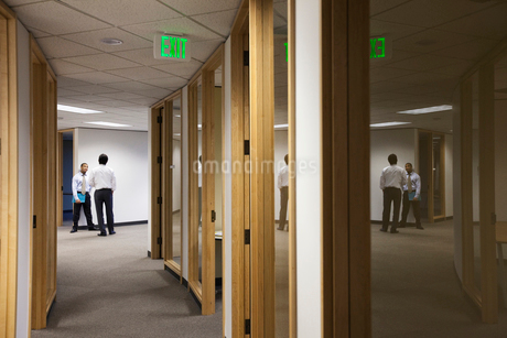 Two business men standing and talking at the end of an office hallway.の写真素材 [FYI02263575]