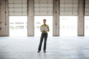 Black woman standing in front of new warehouse loading dock doors and using a lap top computer.の写真素材 [FYI02263580]