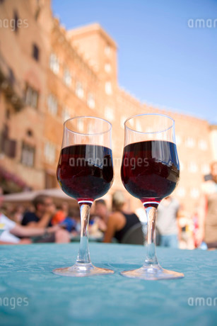 Close up of two glasses of red wine on table, facade of building in background.の写真素材 [FYI02263583]