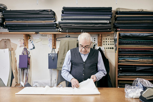 Man inspecting fabric in family-run tailor businessの写真素材 [FYI02263584]