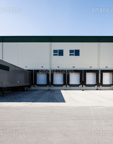 Exterior view of a warehouse loading dock with a truck trailer pulled up to one of the doors.の写真素材 [FYI02263585]