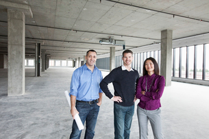 An architect and two owners of a new raw business space standing in a line.の写真素材 [FYI02263589]