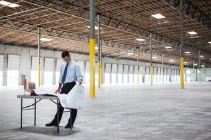 Caucasian man going over plans for new warehouse interior in front of loading dock doors.の写真素材 [FYI02263604]