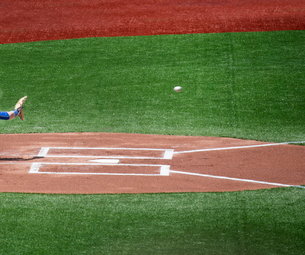Close up of home plate on baseball field, hand with baseball glove about to catch baseball.の写真素材 [FYI02263613]