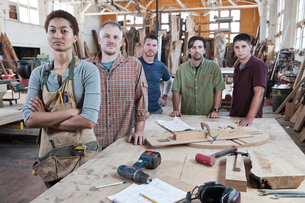 Team of multi-racial factory workers standing next to a work station in a large wood working factoryの写真素材 [FYI02263619]