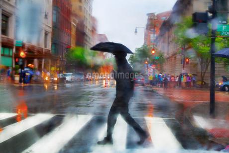 Man carrying umbrella walking across urban street at pedestrian crossing in the rain.の写真素材 [FYI02263620]
