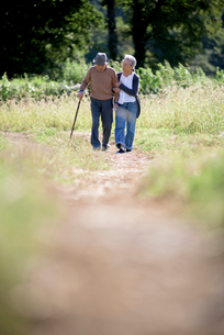 Husband and wife, elderly man wearing hat and using walking stick and elderly woman walking along paの写真素材 [FYI02263621]