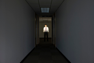 A portrait of a black businessman standing at the end of a long dark hallway.の写真素材 [FYI02263622]
