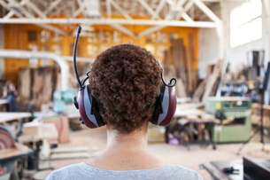 Close up view from behind of a woman factory worker wearing hearing protection in a woodworking factの写真素材 [FYI02263623]
