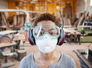 Close up view of black woman factory worker wearing safety glasses and dust nose mask in a woodworkiの写真素材 [FYI02263624]