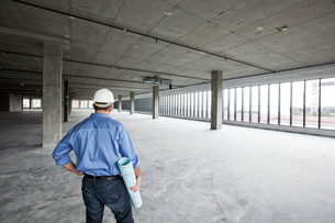 A Caucasian male architect standing looking out over a new raw business space.の写真素材 [FYI02263630]