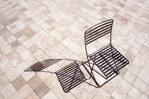 High angle view of black metal folding chair casting shadow onto brown paving.の写真素材 [FYI02263634]