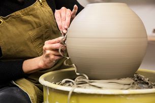 Close up of potter wearing apron working on spherical clay vase on pottery wheel.の写真素材 [FYI02263635]