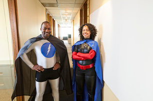 A man and woman team of black office super hero's standing in a hallway of their office.の写真素材 [FYI02263637]