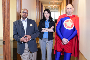 Caucasian middle aged man super hero and his mixed race team staff in their officeの写真素材 [FYI02263639]