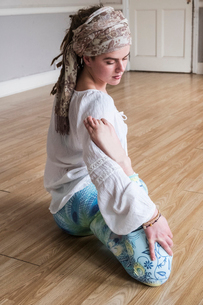 Young woman wearing headscarf and white blouse sitting on floor in yoga pose.の写真素材 [FYI02263640]