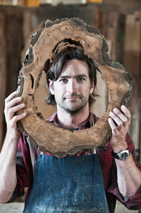 Caucasian man factory worker holding a cut piece from a section of a reclaimed recycled tree in a woの写真素材 [FYI02263648]