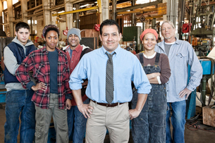Mixed race team of workers and management people in a large sheet metal factoryの写真素材 [FYI02263651]